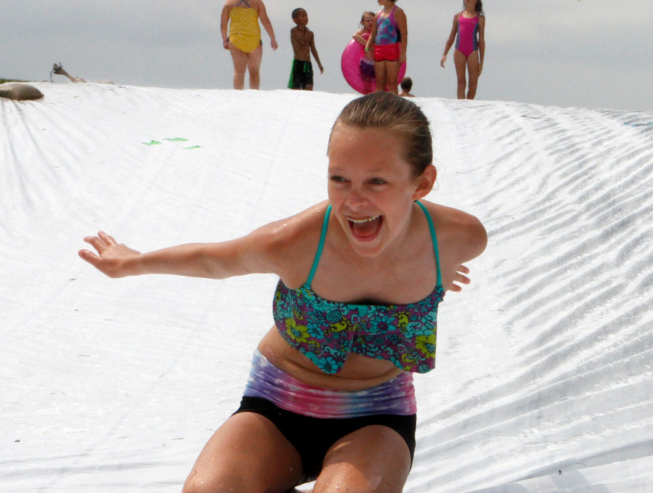 Ella Bishop picks up speed going down a giant slip and slide at Roden Barnyard Adventures on Aug. 9.