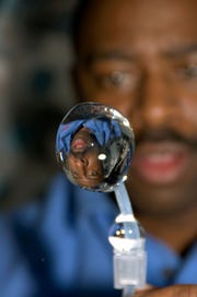 This close-up view of a water bubble floating freely on the space shuttle Atlantis shows a refracted image of astronaut Leland Melvin.