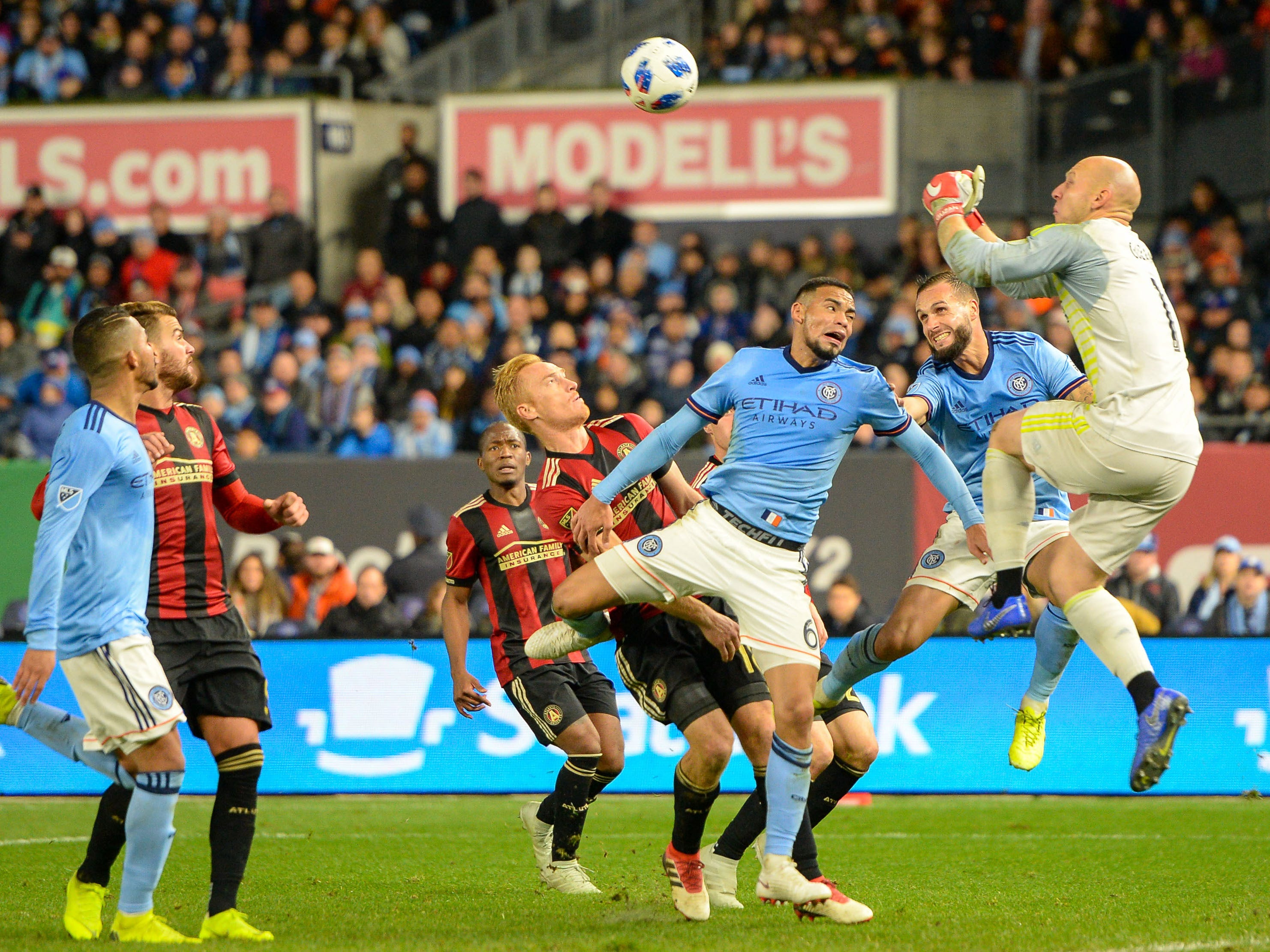 Atlanta United goalkeeper Brad Guzan punches the ball away from New York City FC players during the second half at Yankee Stadium.