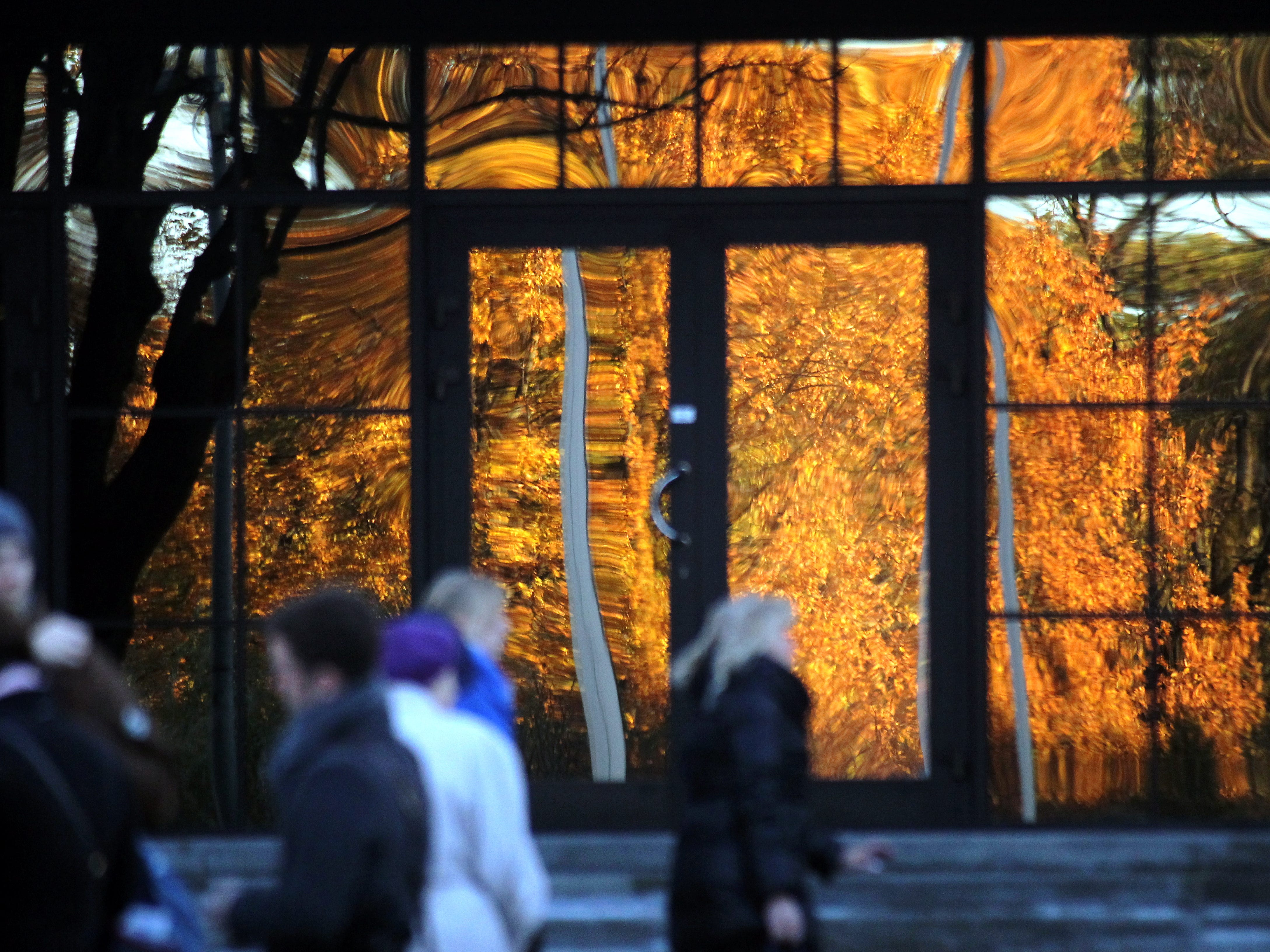 People pass by a house with reflection of autumnal colored trees on a glass wall in Riga, Latvia, Nov. 4, 2018.