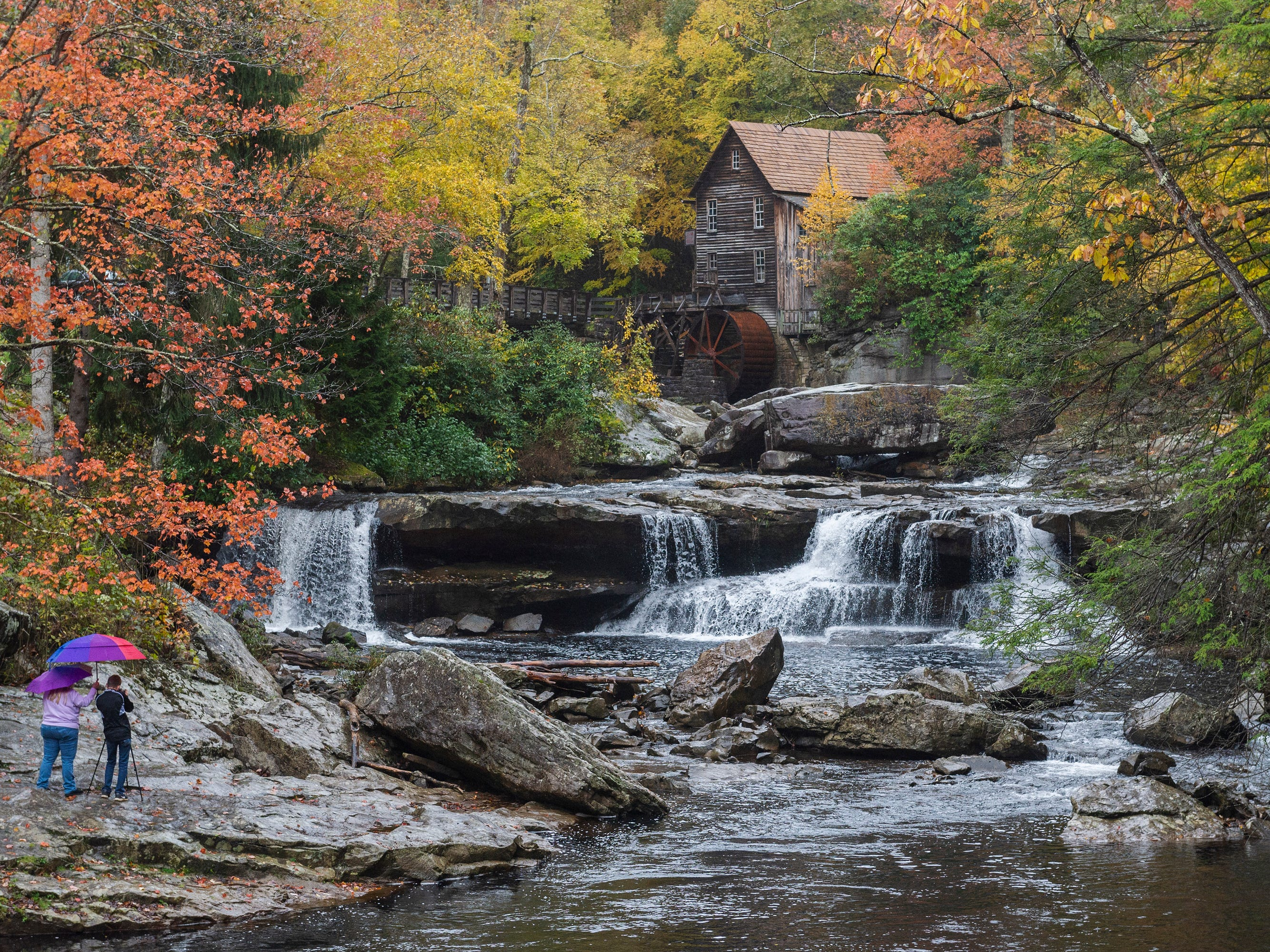 Visitors snap photos on a rainy day amidst fall colors surrounding the Glade Creek Grist Mill inside Babcock State Park near Clifftop, W.Va., on Saturday, Oct. 27, 2018.