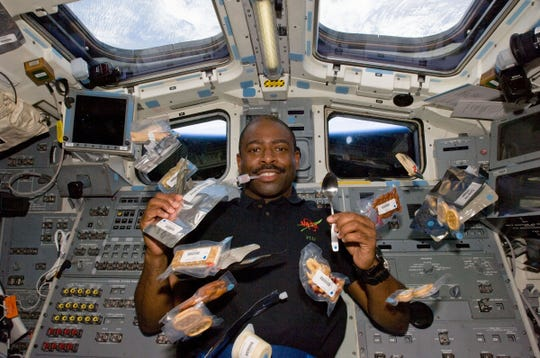 Mission Specialist Leland Melvin poses for a photo on the shuttle Atlantis. Drink and food packets float around him in 2009.