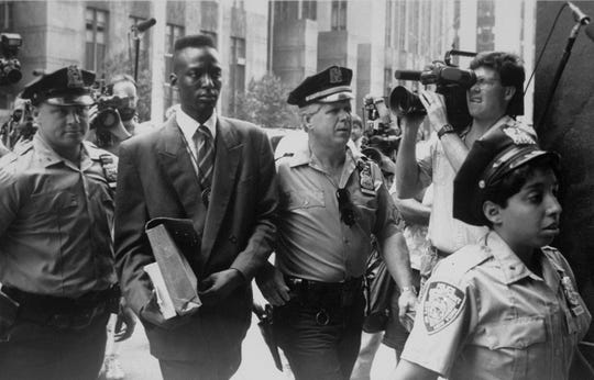 "One of the ""Central Park Five,"" Yusef Salaam is escorted by police in this archival photo."