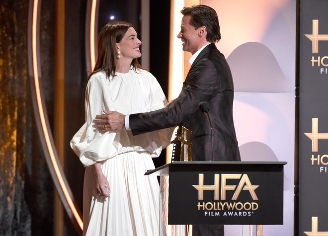 """Anne Hathaway, left, presents the Hollywood actor award to Hugh Jackman for """"The Front Runner""""  at the Hollywood Film Awards."""