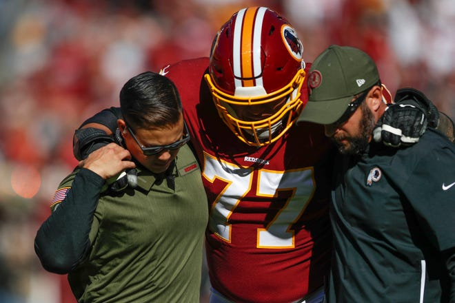 In this Nov. 4, 2018 file photo, Washington Redskins offensive guard Shawn Lauvao (77) is helped off the field after an injury during the first half of an NFL football game between the Atlanta Falcons and the Washington Redskins, in Landover, Md. Both starting guards for the Washington Redskins, Lauvao and Brandon Scherff, will have season-ending surgery, as will wide receiver Paul Richardson.