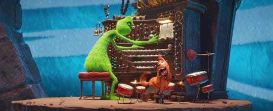 "The Grinch (Benedict Cumberbatch) plays the organ with a little help from his dog Max on drums in ""The Grinch."""