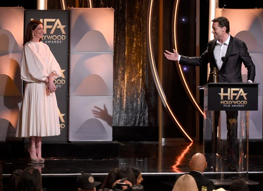 "Hugh Jackman, right, gestures to presenter Anne Hathaway as he accepts the Hollywood actor award for ""The Front Runner"" at the Hollywood Film Awards."