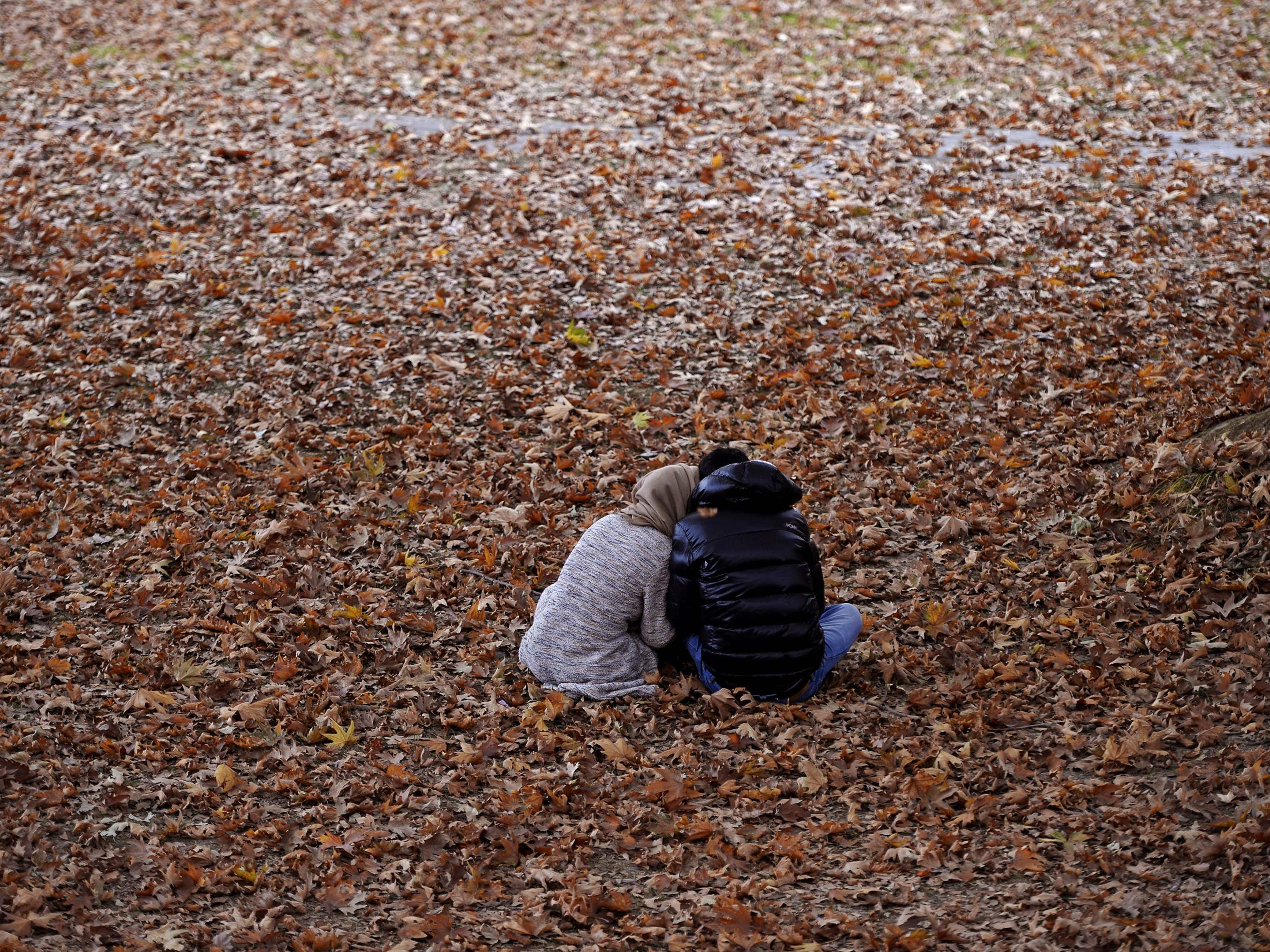 A Kashmiri couple sits amongst tree leaves during the autumn season in Srinagar, India, on Nov. 1, 2018.