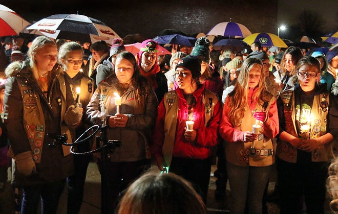 Girl Scouts sing as hundreds of community members turn out in the rain on Nov. 4, 2018, for a candlelight vigil at Halmstad Elementary School in Chippewa Falls, Wis.