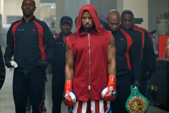 Michael B. Jordan (in hoodie) stars as Adonis Creed. The man to his right holding a belt is Jordan's trainer Cory Calliet, who has a part in the film as Creed's cornerman.