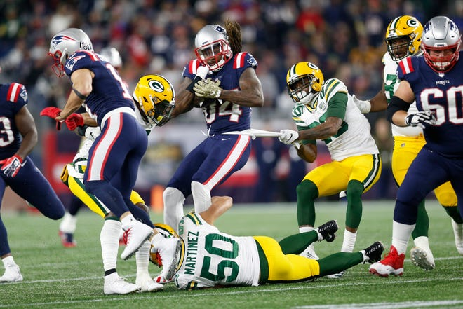New England Patriots wide receiver Cordarrelle Patterson (84) is a tackled by Green Bay Packers inside linebacker Blake Martinez (50) and defensive back Bashaud Breeland (26) during the second quarter at Gillette Stadium.