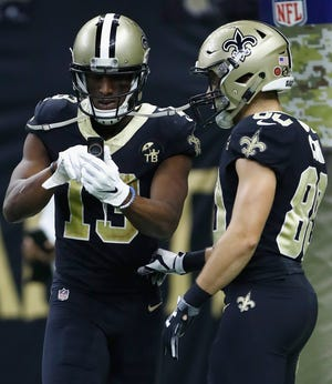 Michael Thomas pretends to make a call on a cellphone that he dug out from under the goal post in celebration of a touchdown against the Los Angeles Rams at Mercedes-Benz Superdome.