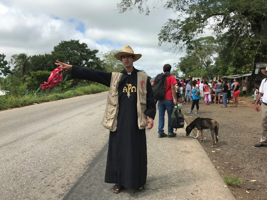 Brother Jonathan Ortiz of the Missionaries of the Risen Christ religious order flags down a car near Sayula de Aleman in Mexico's Veracruz state on Nov. 3, 2018. Members of Ortiz's religious order attempted to help participants in the caravan of Central American migrants get rides as it moved north through a dangerous part of Mexico.