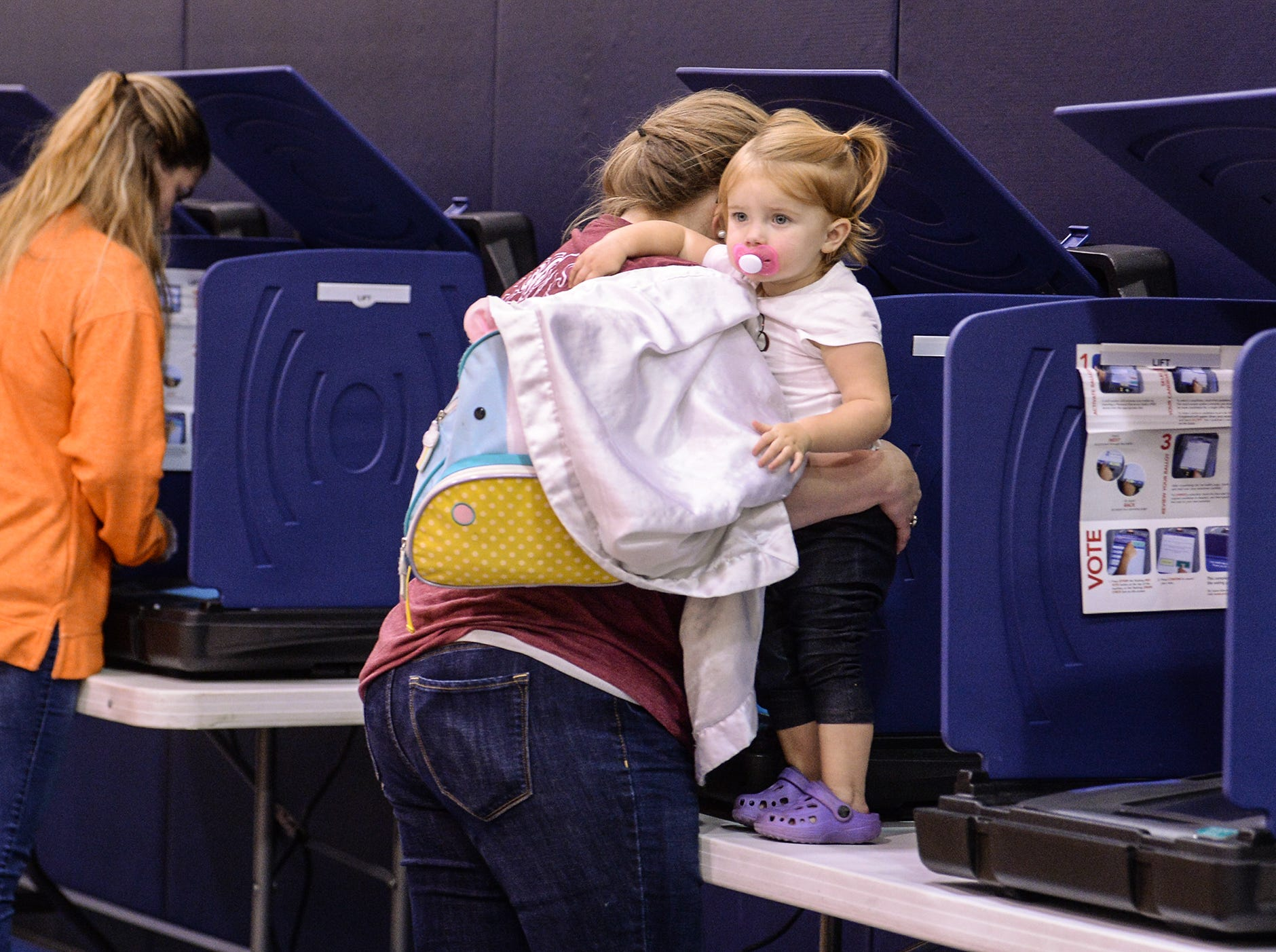 Judith Lee Carson, holding her daughter Harper, votes shortly after lunch hour at the Hammond precinct at Midway Elementary in Anderson on Tuesday, November 6, 2018. Hammond precinct had over 800 vote by lunch, one of the busiest in the county.