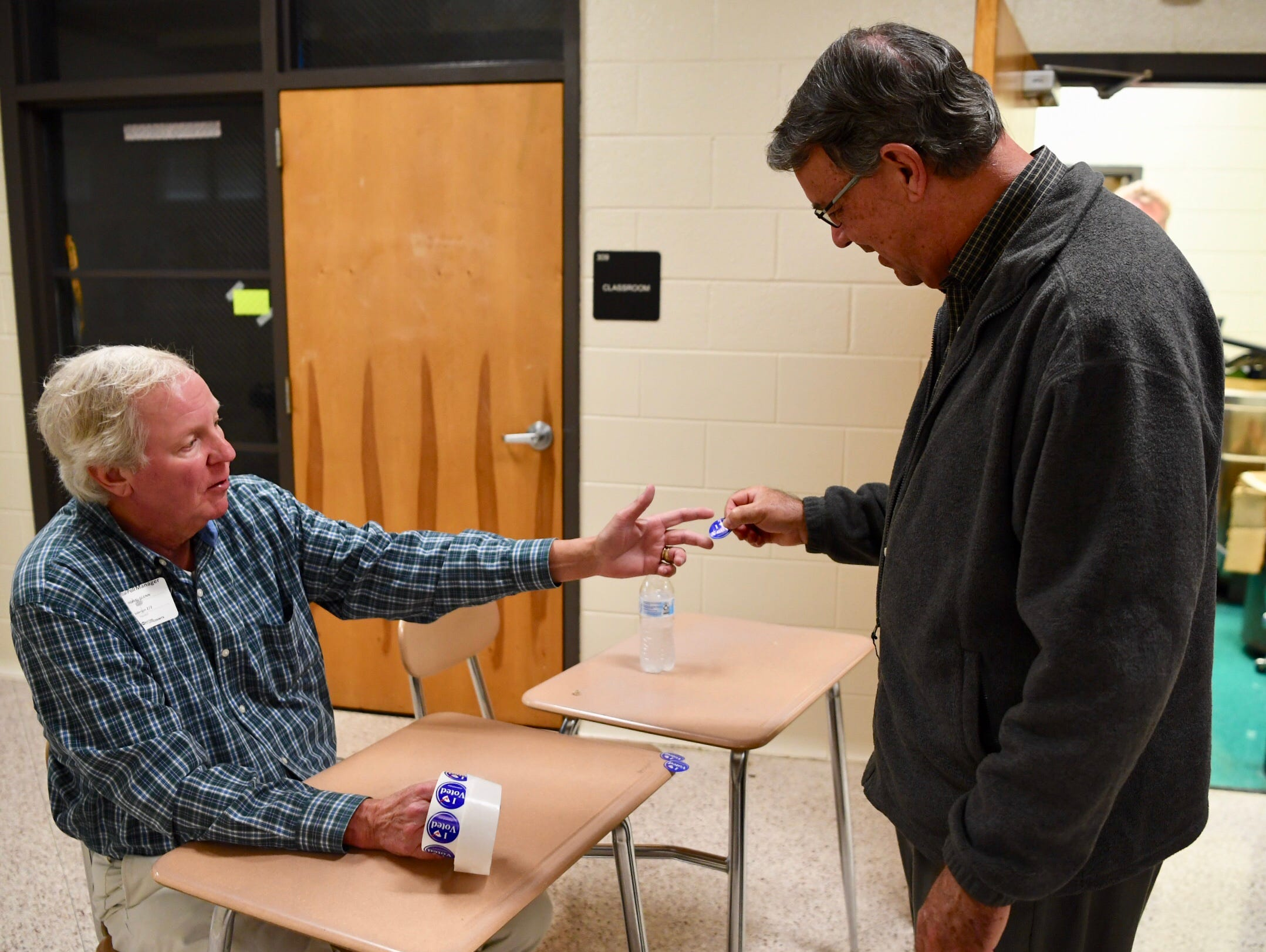 The Rev. Jim Thomason of First Baptist Church in Anderson gets a sticker from Mike Glenn a poll manager at McCants Middle School in Anderson.