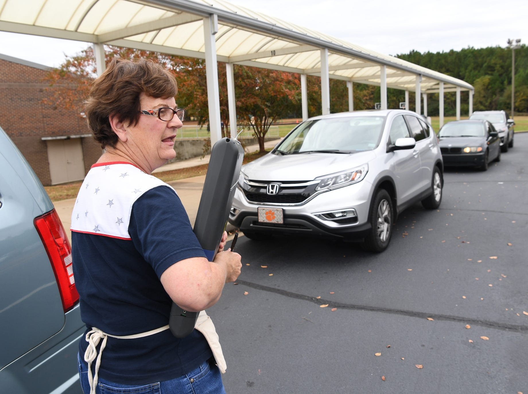 Melanie Thorne, poll clerk of Hammond precinct at Midway Elementary in Anderson, helps Mike Mitchell with curbside voting in his car on Tuesday, November 6, 2018.