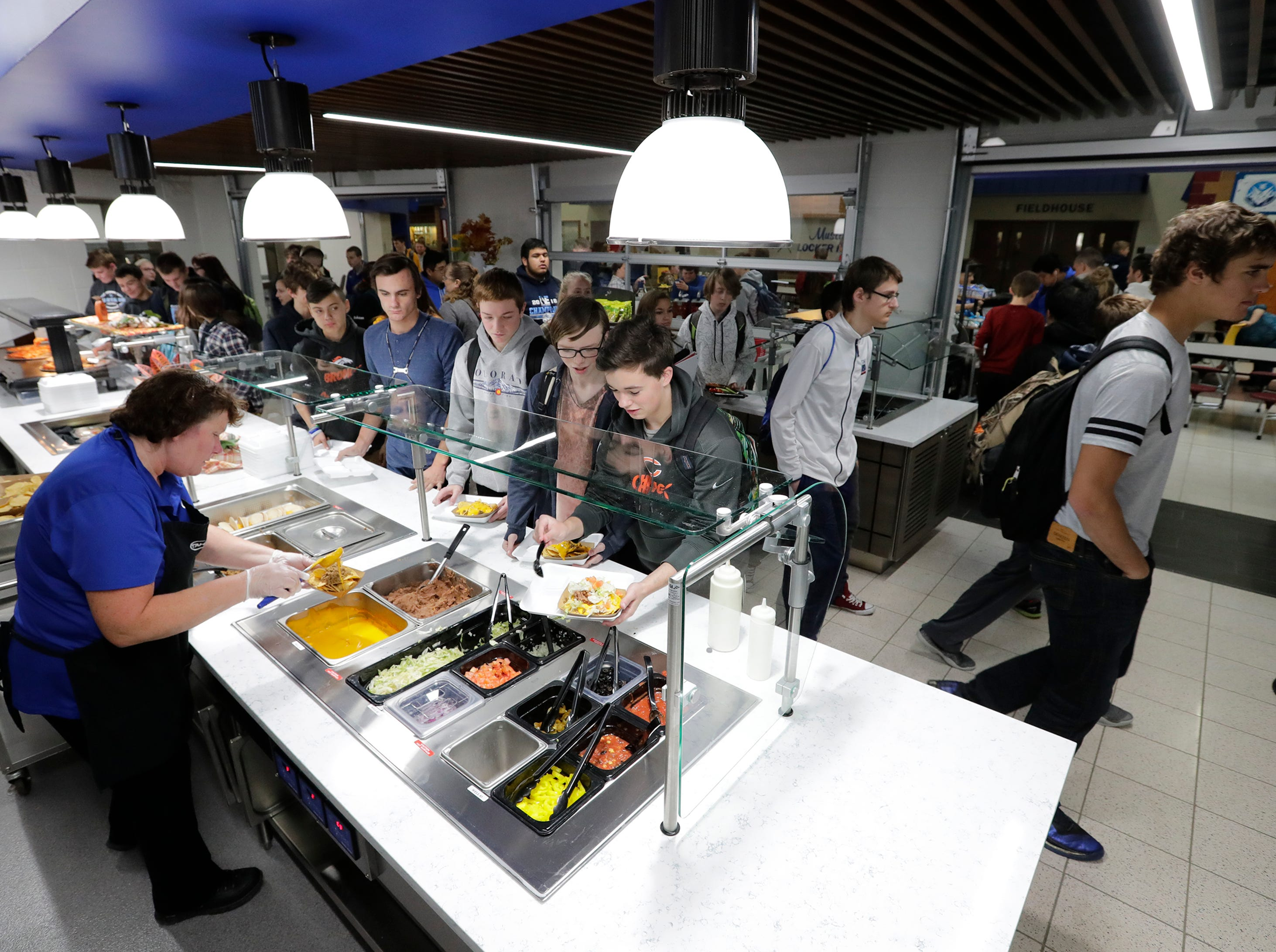 Sherrie Hoelzel, left, serves lunch to students in part of the new dining area at Little Chute High School Tuesday, November 6, 2018, in Little Chute, Wis. 