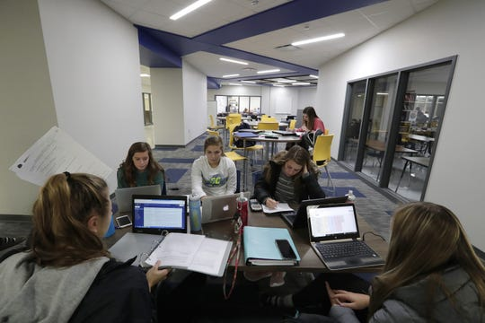 A group of senior students hang out Tuesday in a collaboration area at the newly renovated Little Chute High School.