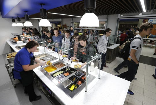 Sherrie Hoelzel serves lunch Tuesday to students in part of the new dining area at Little Chute High School. The school facility houses the intermediate, middle and high schools.
