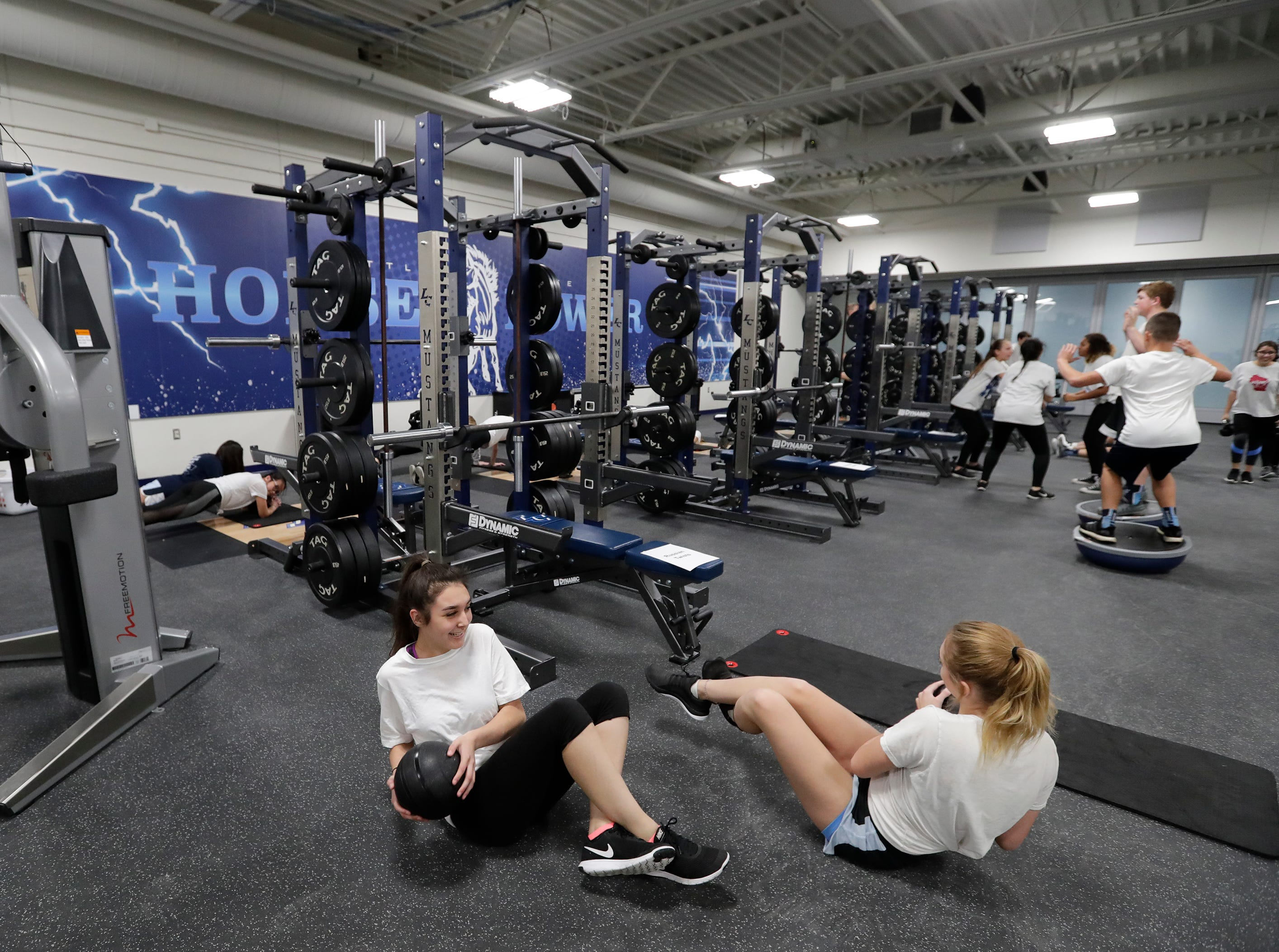 Angel Sanchez, left, and Madison Withrow participate in the Intro to Strength and Conditioning class in the new fitness center at Little Chute High School Tuesday, November 6, 2018, in Little Chute, Wis. 