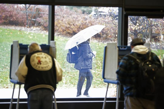 A student walks past as voters cast their ballots at the UW-Green Bay campus on Tuesday in Green Bay.