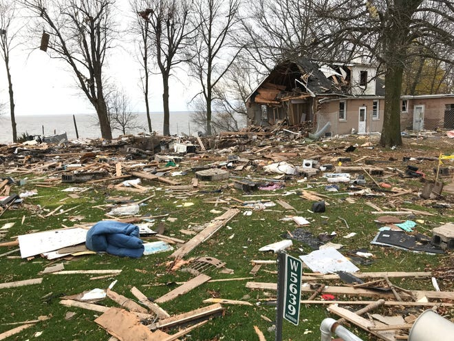 Debris from a house that exploded on Oct. 10 in Harrison remains scattered around the neighborhood. The house was located near the trees on the left side of the photo. The damaged house on the right side of the photo belongs to a neighbor.