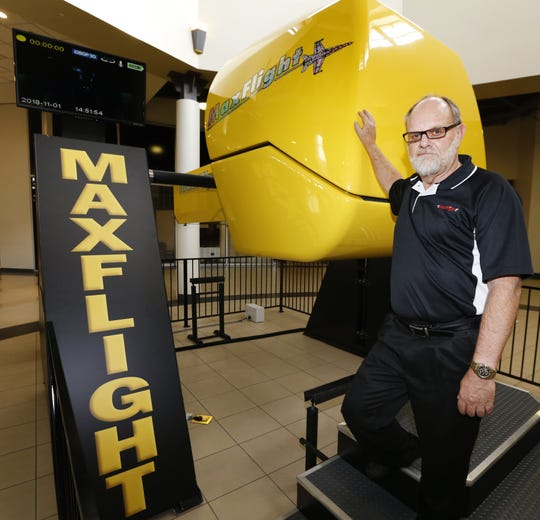 Frank McClintic, owner of Maxflight Corp., next to a flight simulator at Monmouth Mall in Eatontown.