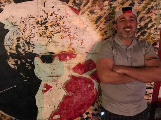 Owner Anthony Esposito with a detail of the Bob Dylan mural at the Inkwell in Long Branch.