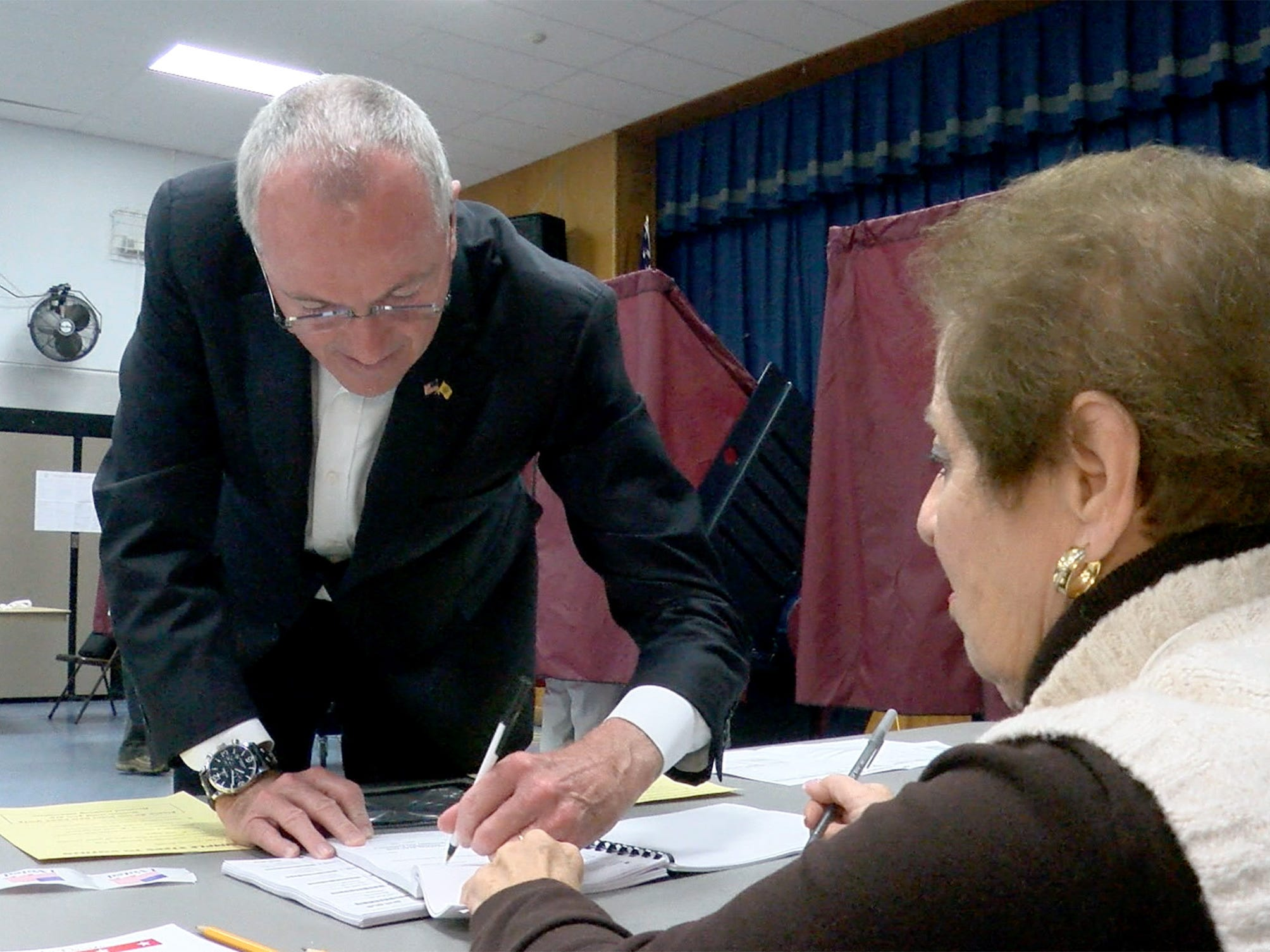 NJ Governor Phil Murphy signs in with a poll worker as he prepares to vote at the Fairview Elementary School in Middletown Tuesday, November 6, 2018.