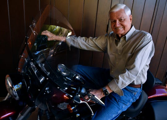 Jack Ramsey sits astride his Harley-Davidson motorcycle. He also owns an Aston Martin.