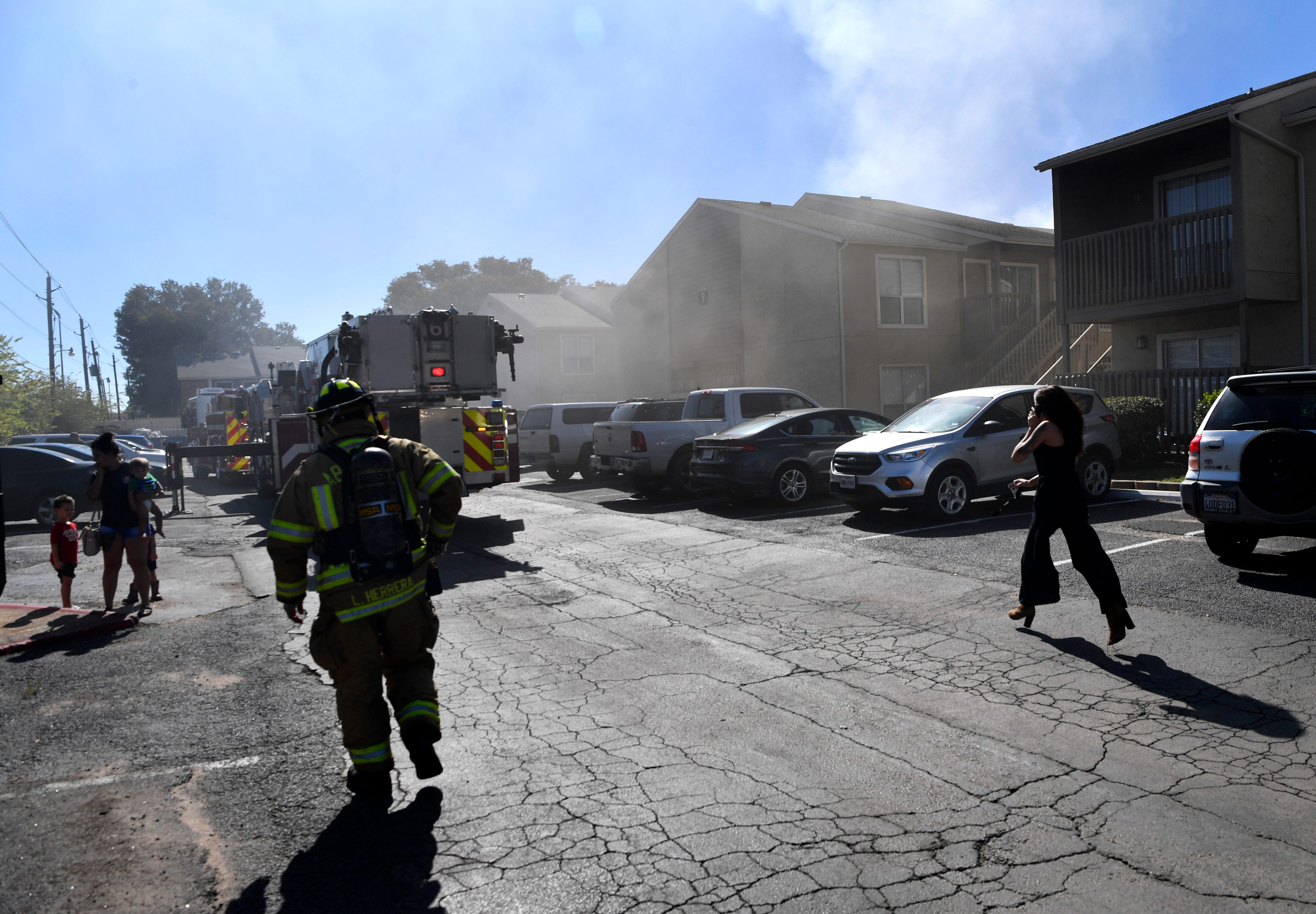 A woman runs to the scene of a fire at Indian Run Apartments Tuesday. The south Abilene, two-alarm fire started around 1 p.m.