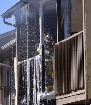 An Abilene firefighter digs at the roof covering a patio at Indian Run Apartments Tuesday. A two-alarm fire broke out around 1 p.m., damaging at least two apartments.