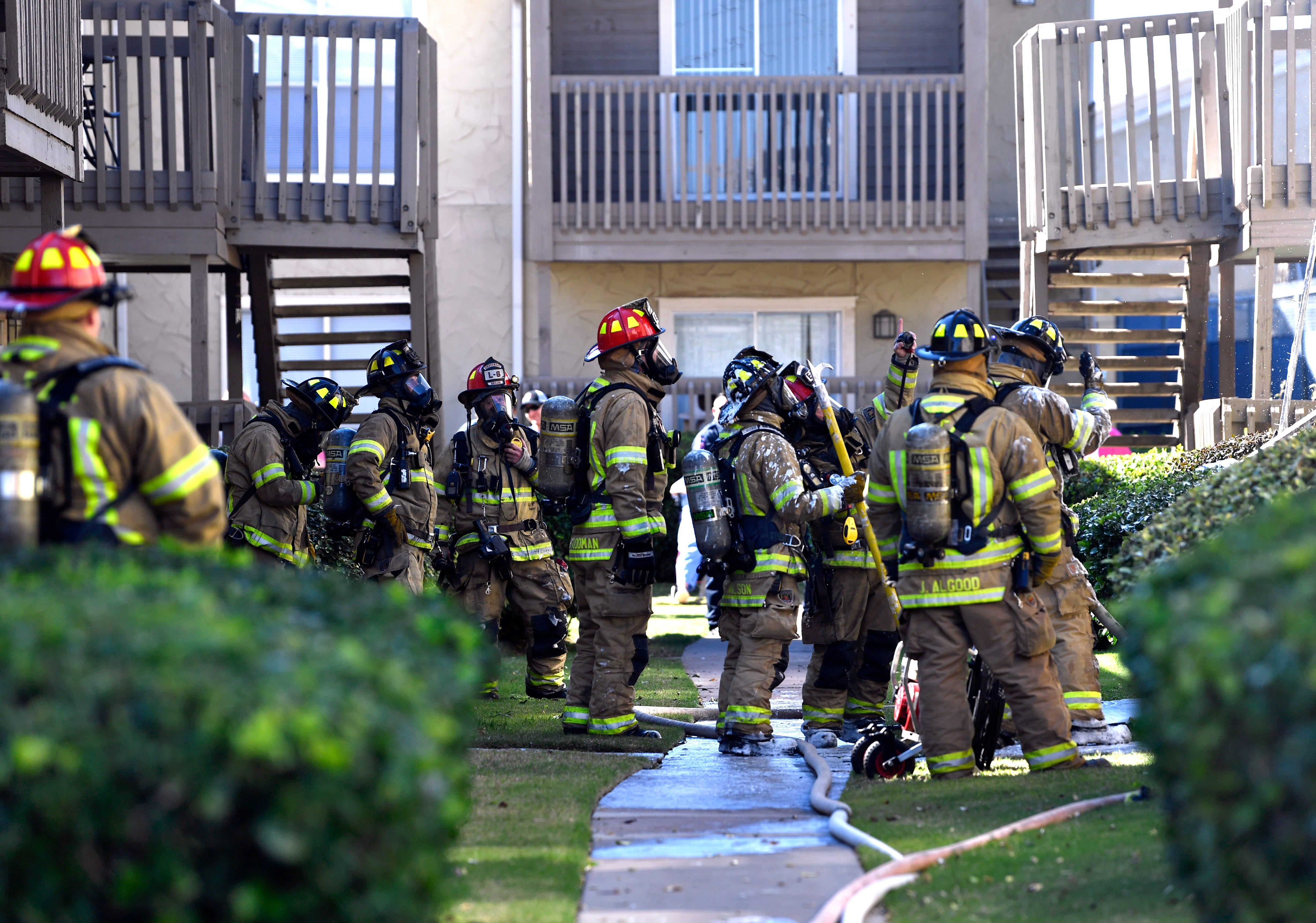 Abilene firefighters standby to assist as others department members fight a fire inside a residence at Indian Run Apartments Tuesday.