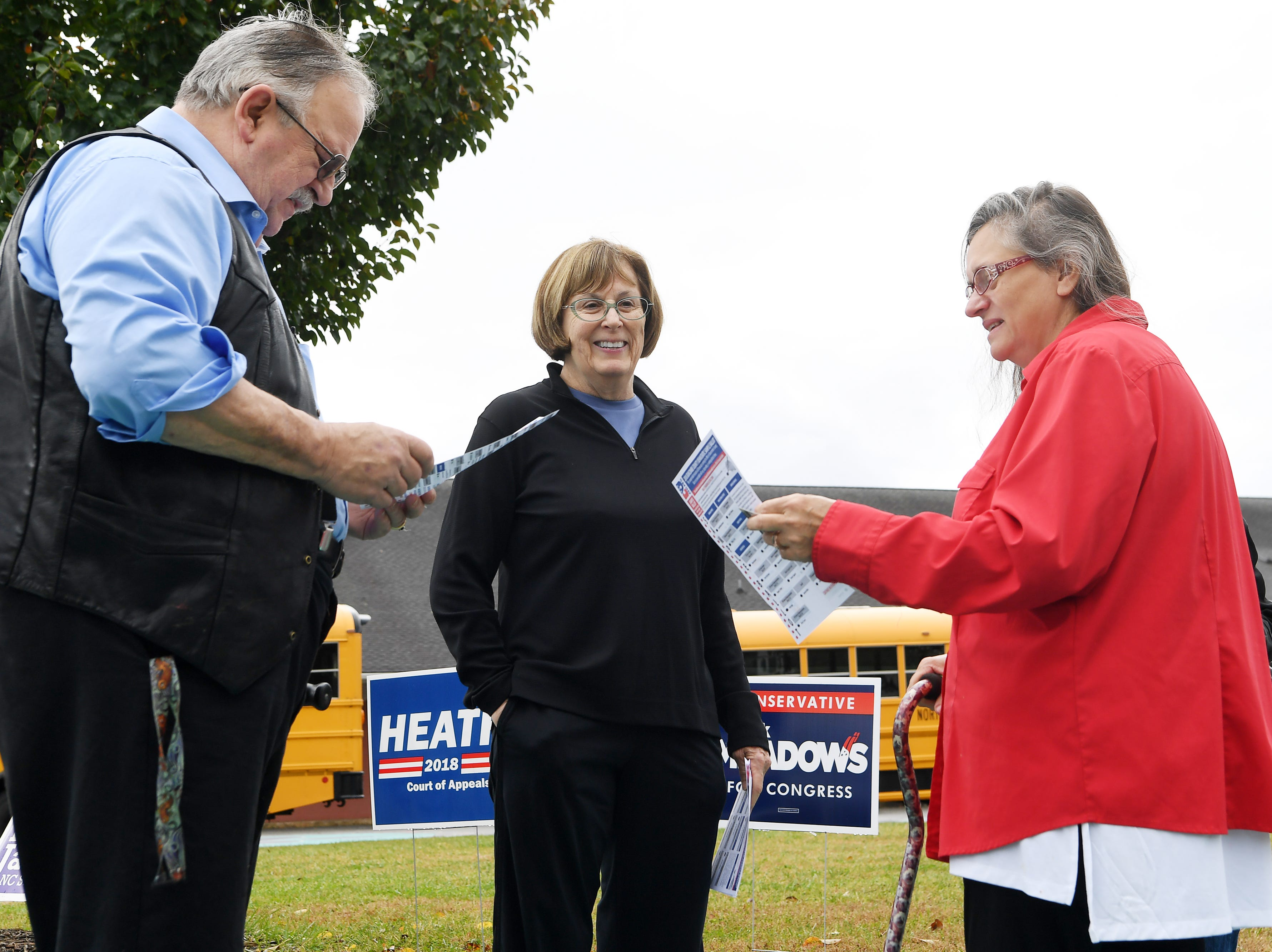 "Buncombe County Democrats volunteer Jacie Logan, center, talks with Bruce Kline and Martiy Munden as they view a sample ballot at Emma Elementary Nov. 6, 2018. ""I brought my new heart with me to vote,"" said Munden, who had a heart transplant this summer."