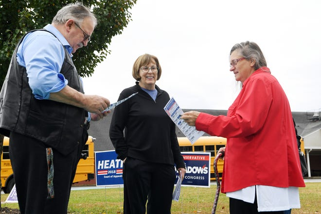 """Buncombe County Democrats volunteer Jacie Logan, center, talks with Bruce Kline and Martiy Munden as they view a sample ballot at Emma Elementary Nov. 6, 2018. """"I brought my new heart with me to vote,"""" said Munden, who had a heart transplant this summer."""