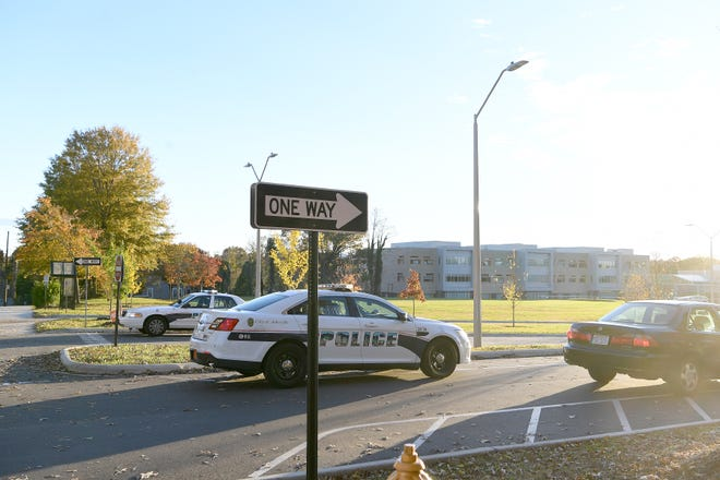 """Officers and school officials stop cars as they arrive at Asheville Middle School to pick up students following what was described as a """"credible threat"""" made against the school on Nov. 6, 2018."""