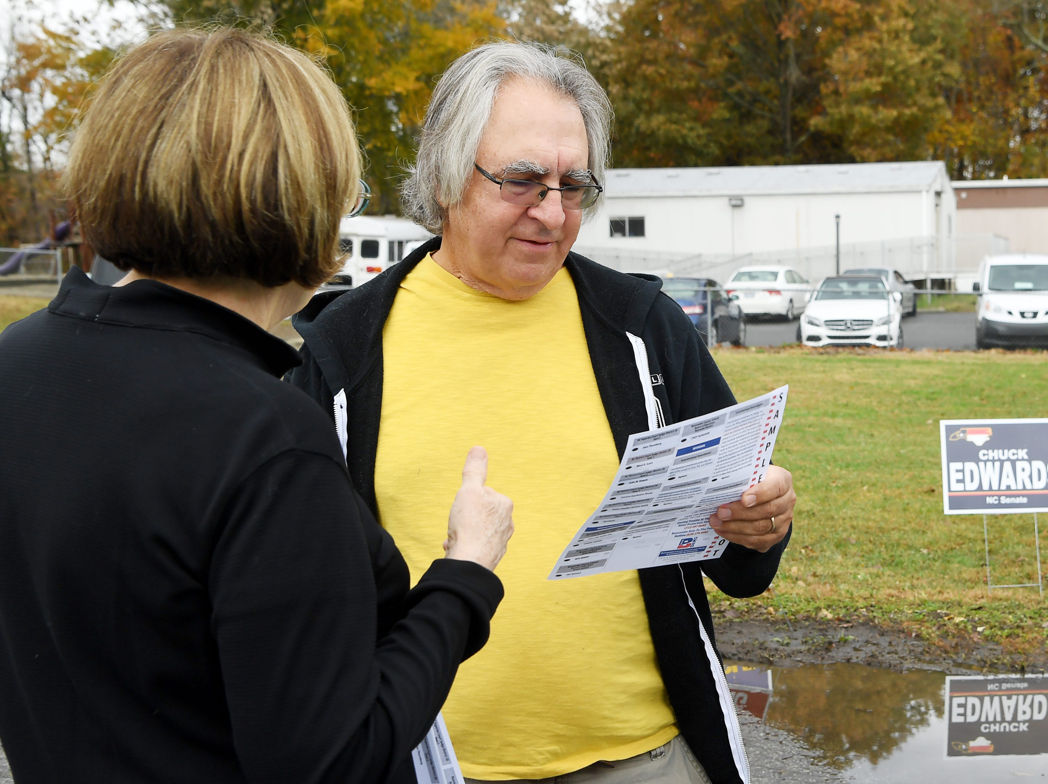 Mike Leippe views a sample ballot with Buncombe County Democrats volunteer Jacie Logan before voting at Emma Elementary Nov. 6, 2018.