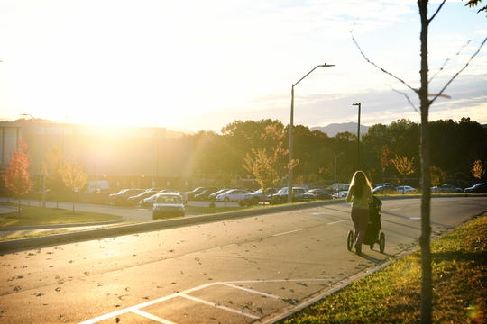 "Katie Winton walks her daughter in a stroller to pick up her seventh grade student at Asheville Middle School following what was described as a ""credible threat"" made against the school on Nov. 6, 2018."
