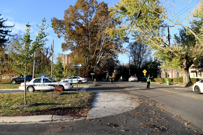 """Officers direct traffic on French Broad Avenue at Asheville Middle School following what was described as a """"credible threat"""" made against the school on Nov. 6, 2018."""