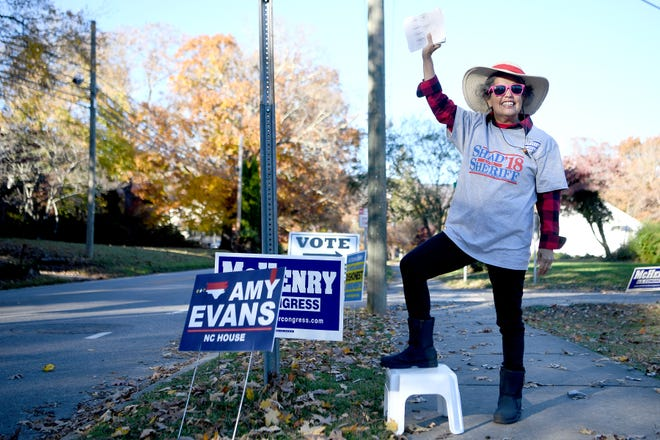 """Sylvia Arrowood waves to motorists as she campaigns for Shad Higgins outside of the First Baptist Church of Black Mountain on Nov. 6, 2018. """"He believes in the constitution and he believes in enforcing the law and he wants to clean the county up from illegal drugs and crime,"""" she said about her support of Higgins."""