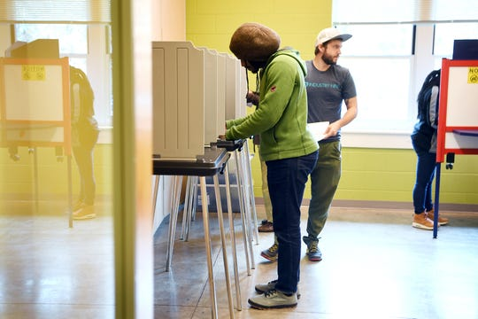Trey Thomas, left, fills out his ballot at the Dr. Wesley Grant Southside Center on Election Day Nov. 6, 2018.