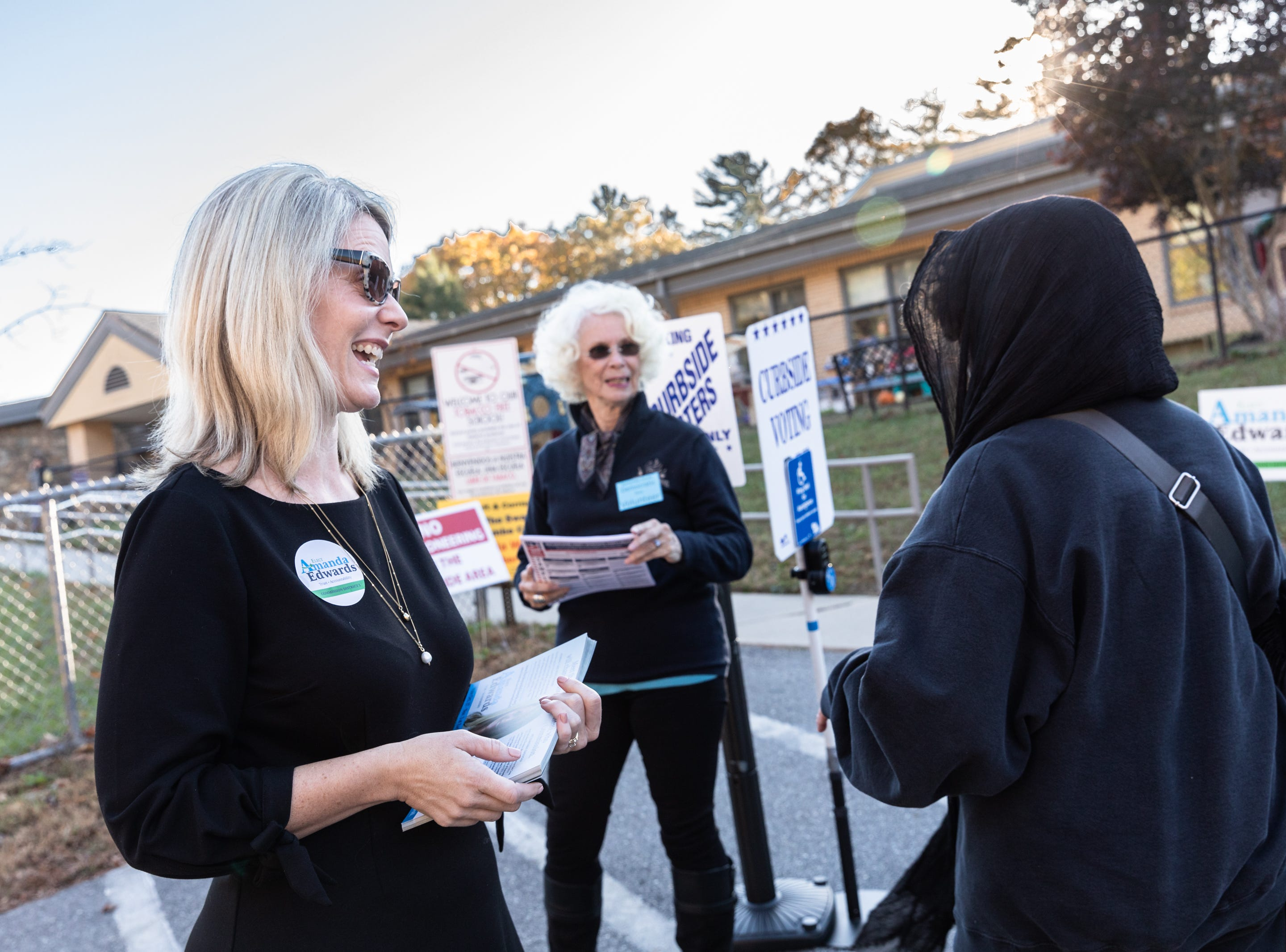 Amanda Edwards, Democratic candidate for the district 2 Buncombe County Commission, talks with a voter at Ira B. Jones elementary school, one of the midterm election voting sites, Nov. 6, 2018.