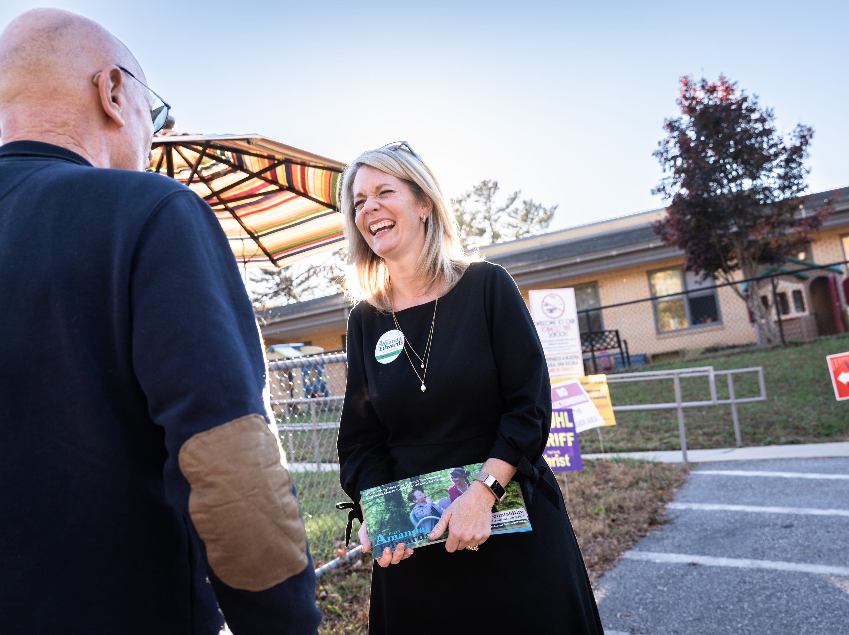 Amanda Edwards, Democratic candidate for the district 2 Buncombe County Commission, talks with a Democratic Party volunteer at Ira B. Jones elementary school, one of the midterm election voting sites, Nov. 6, 2018.