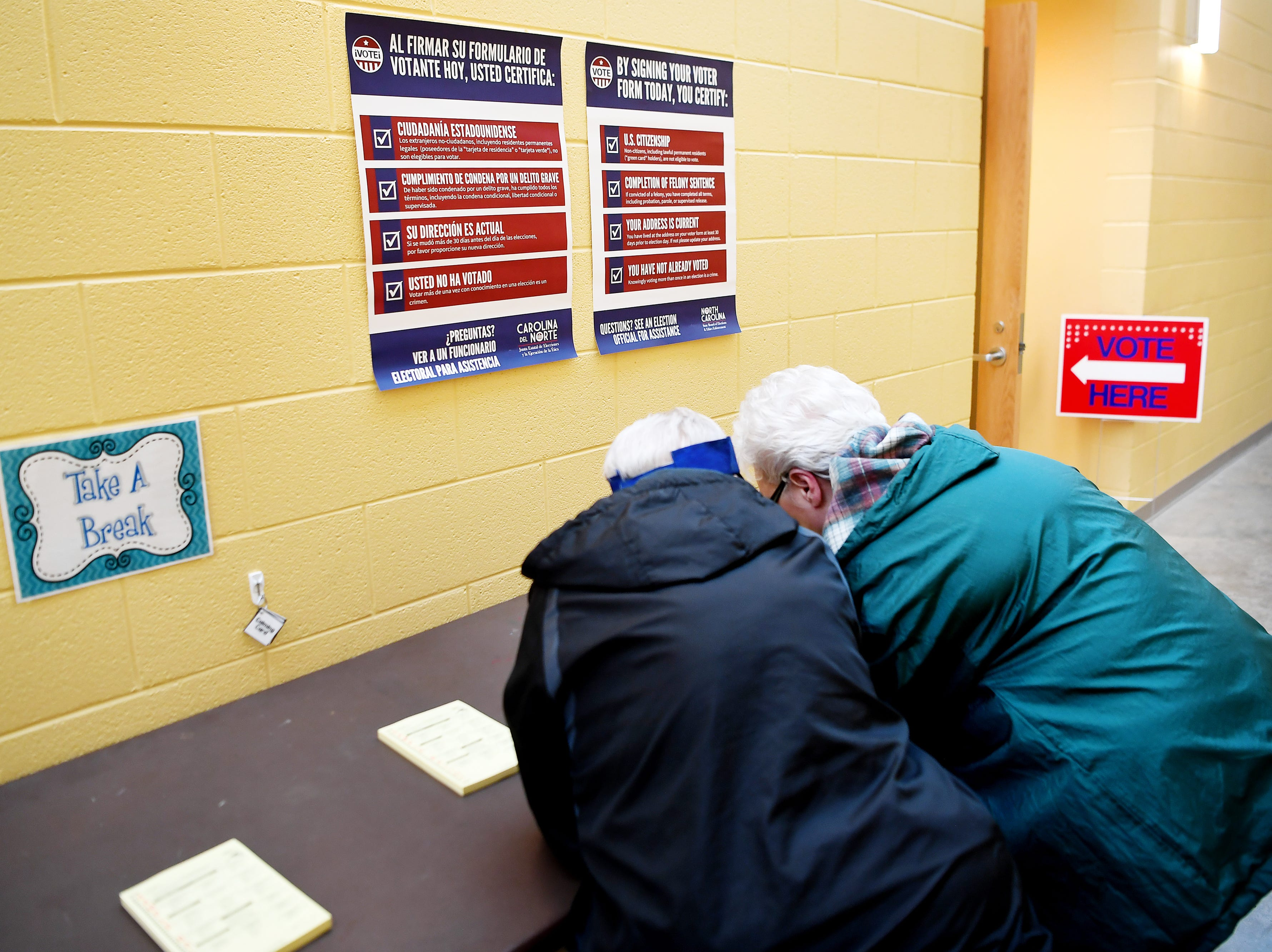 Vinnie Whitted, left, and Ann Whitner huddle together as they examine at sample ballot before casting their vote at the Dr. Wesley Grant Southside Center Nov. 6, 2018.