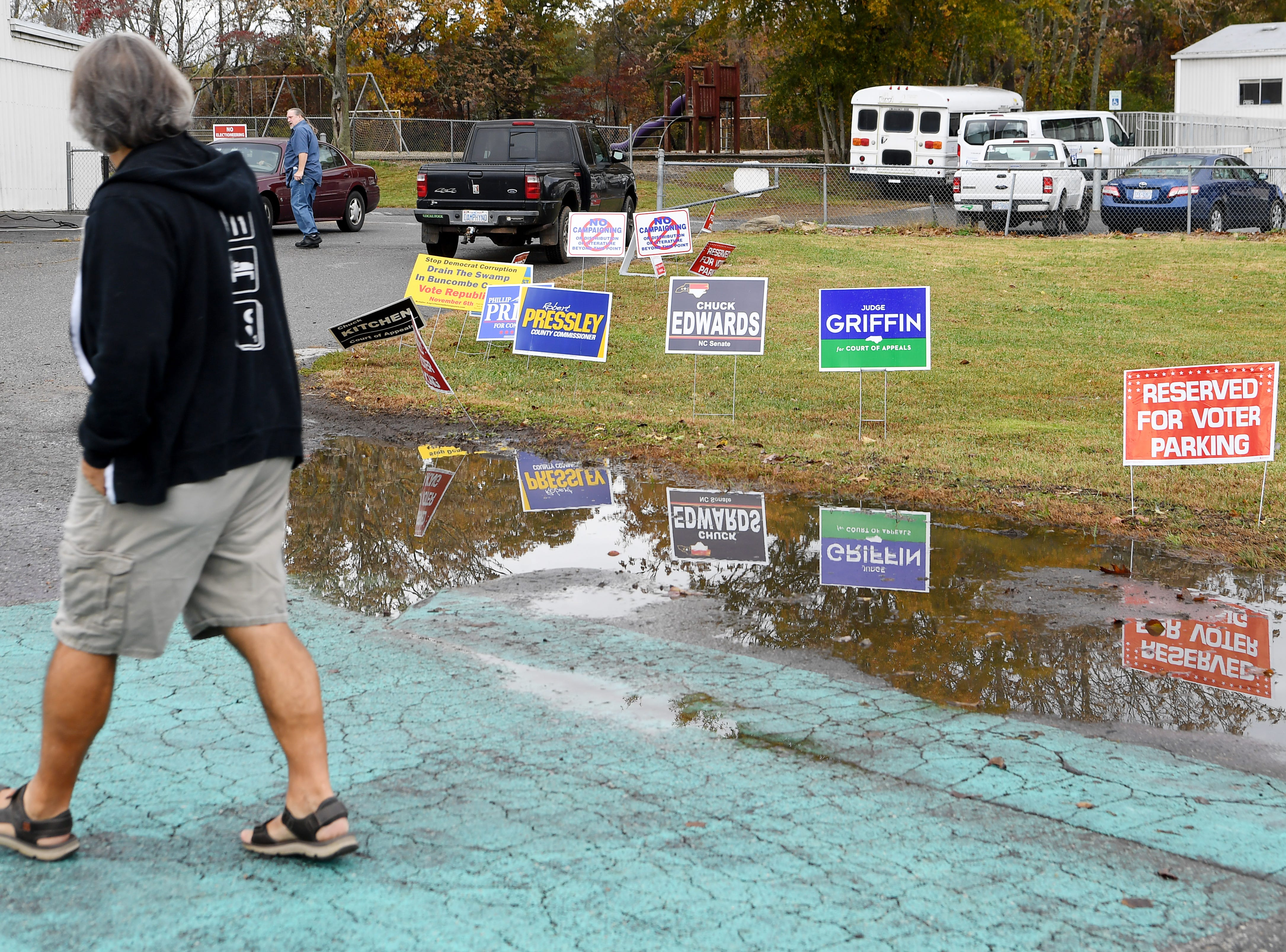 Campaign signs are reflected in a puddle after a morning rain Nov. 6, 2018 at Emma Elementary.
