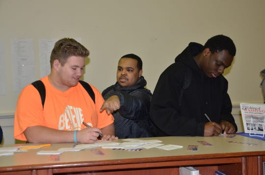 A group of Battle Creek Central students sign in to vote during Tuesday's mock election. Pictured, from left, senior Jesse Ackley, junior Melvin White and senior Quinterious Brown.