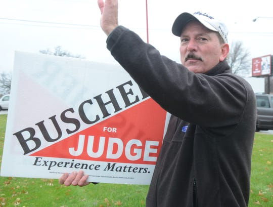 Despite some afternoon rain, Dan Buscher was waving to passing motorists Tuesday afternoon on 24th Street near Columbia Avenue.