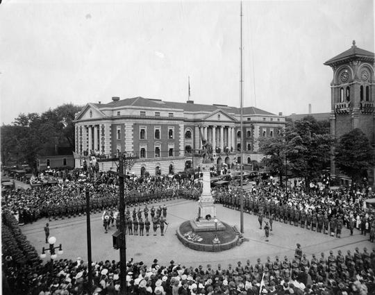 This May 30, 1918 photo shows a flag pole dedication in front of City Hall and the First Methodist Church.