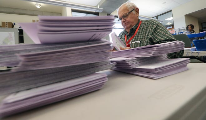 Elections worker Jerry Preuss removes ballots from their envelopes while processing votes at the Kitsap County Elections Office in Port Orchard on Tuesday, November 6, 2018.
