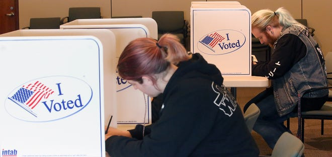 Port Orchard residents Amanda Reynolds (front) and Hazel Ash (back) fill out their ballots at the Kitsap County Administration Building on Tuesday, November 6, 2018.